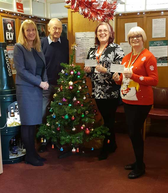 Belinda Sutton and Nigel Elgood present the cheques to representatives of the Arthur Rank Hospice and East Anglia Air Ambulance